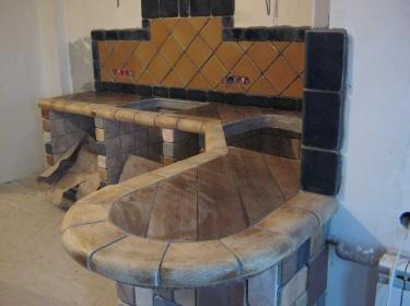 Криволинейная рабочая поверхость на кухне по краю окантована шамотными элементами.